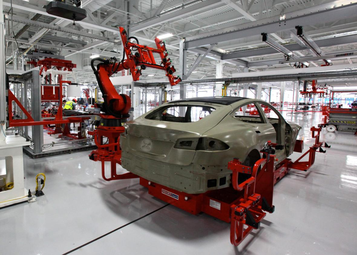 Tesla factory where a robot installs the laminated glass roof on a Model S.