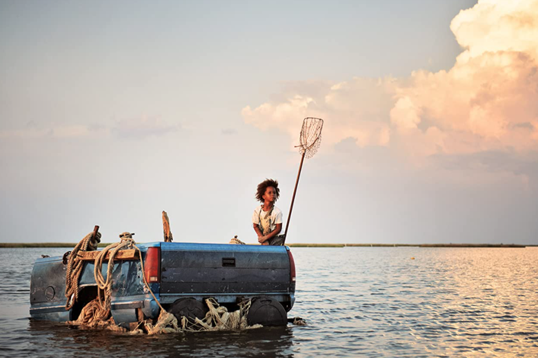 Quvenzhané Wallis sits on the bed of a pickup truck floating in a vast lake of water.