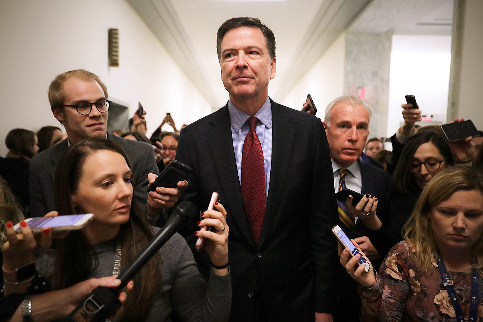 James Comey mobbed by reporters.