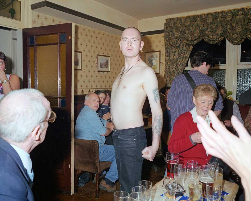 A bare chested skinhead postures for the camera in a pub in Bacup, Lancashire.