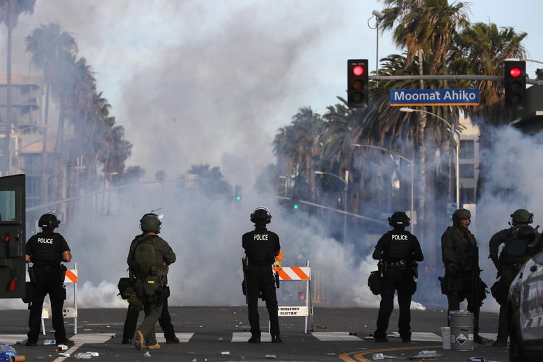 Police watch as tear gas is deployed during demonstrations in the aftermath of George Floyd's death.