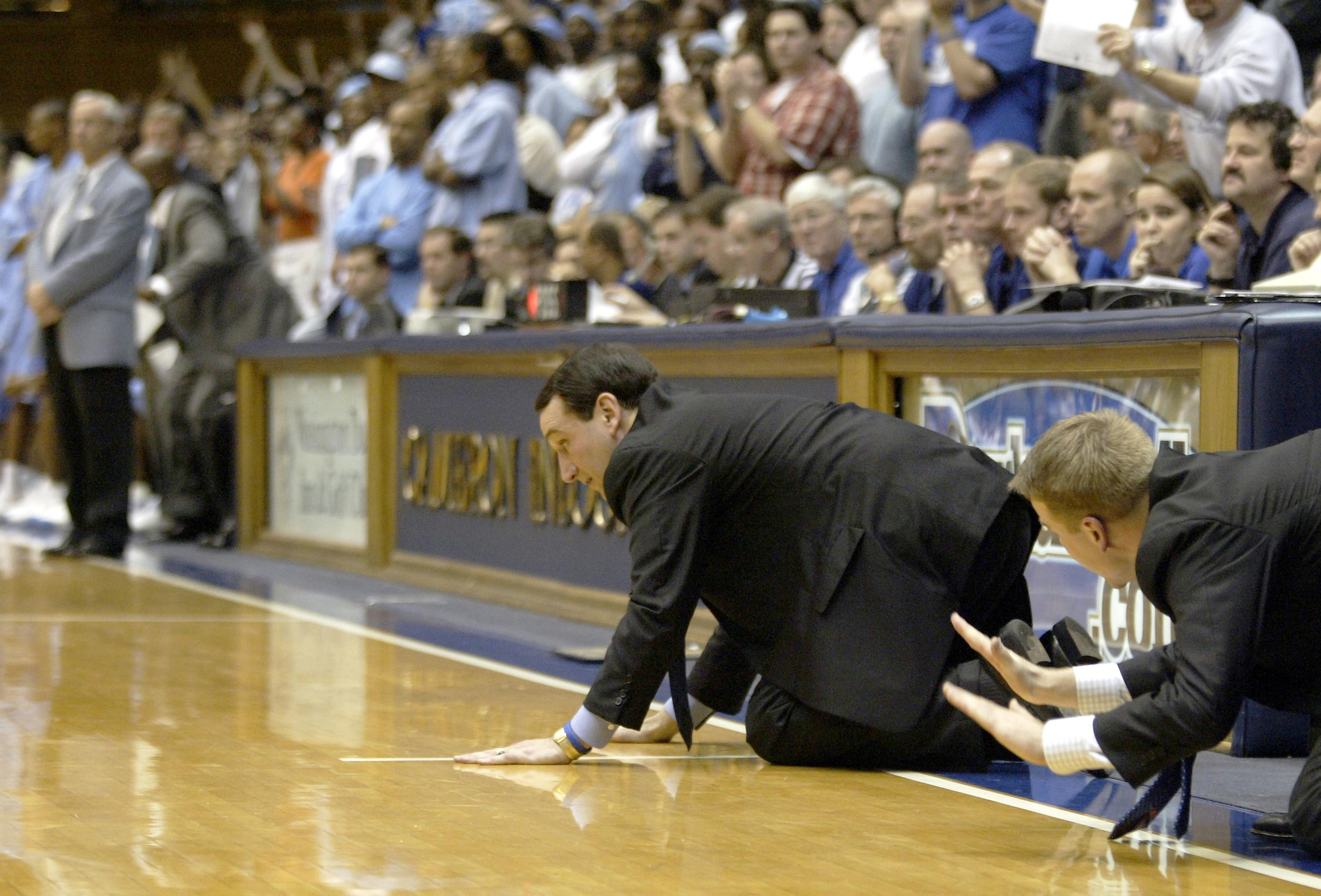 DURHAM, NC - FEBRUARY 9:  Head coach Mike Krzyzewski and assistant coach Steve Wojciechowski (R) of the Duke Blue Devils slap the floor to signal defense during their game against the North Carolina Tar Heels at Cameron Indoor Stadium on February 9, 2005 in Durham, North Carolina. Duke defeated North Carolina 71-70.  (Photo by Craig Jones/Getty Images)