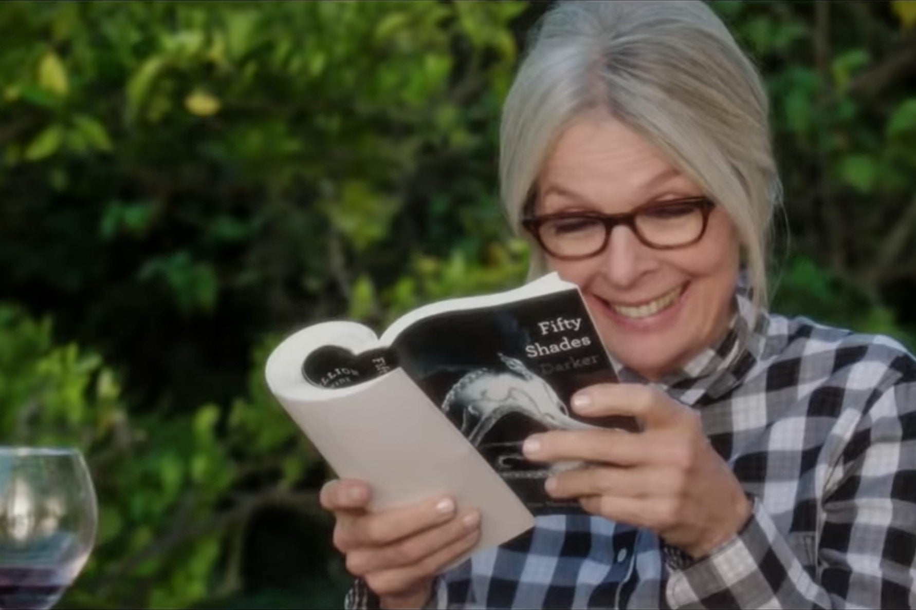 Diane Keaton grins while reading Fifty Shades of Grey in the movie Book Club.