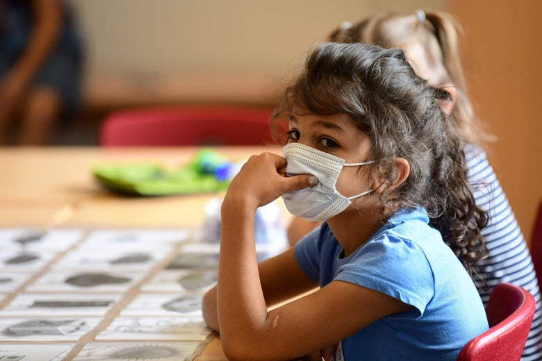 A girl, wearing a face mask, sits at a school desk, apparently listening to her teacher.