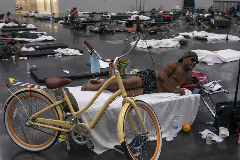 A man rests on a cot in a cooling center, along with his bike.