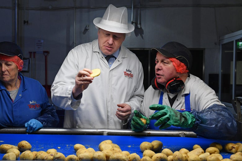 Boris Johnson inspects a potato while he and two workers stand in front of a conveyor belt of potatoes.