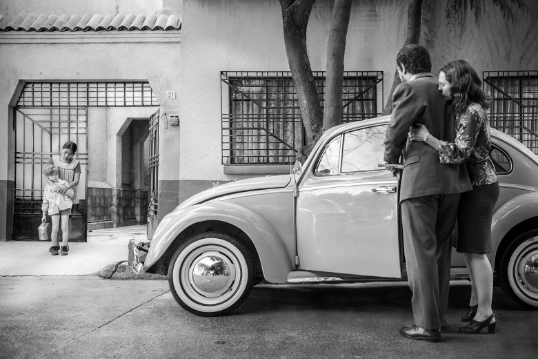 In a still from Roma, a woman clings to her husband beside their car, and a maid comforts their child outside the gate of their home.