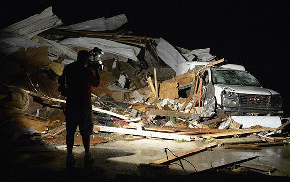 News video photographer Brad Mack covers the damage seen after a tornado hit the town of Mayflower, Arkansas.