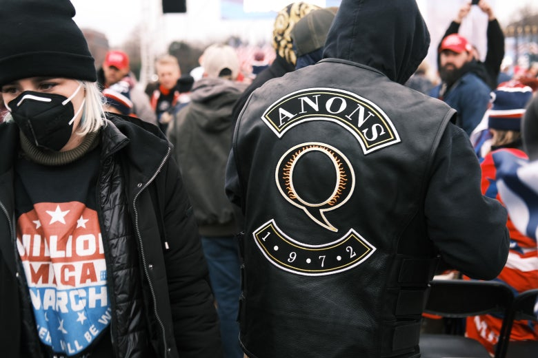 A man in a QAnon jacket at a rally.