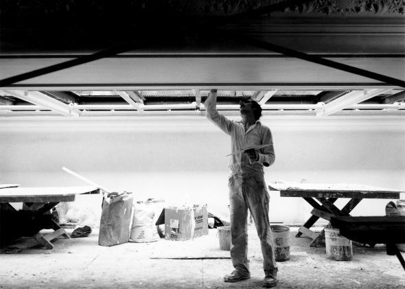 A man works on restoring the glass skylights.
