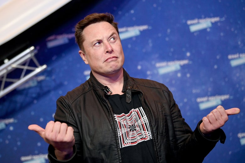 Elon Musk, onstage at an event, points his thumbs in two separate directions.