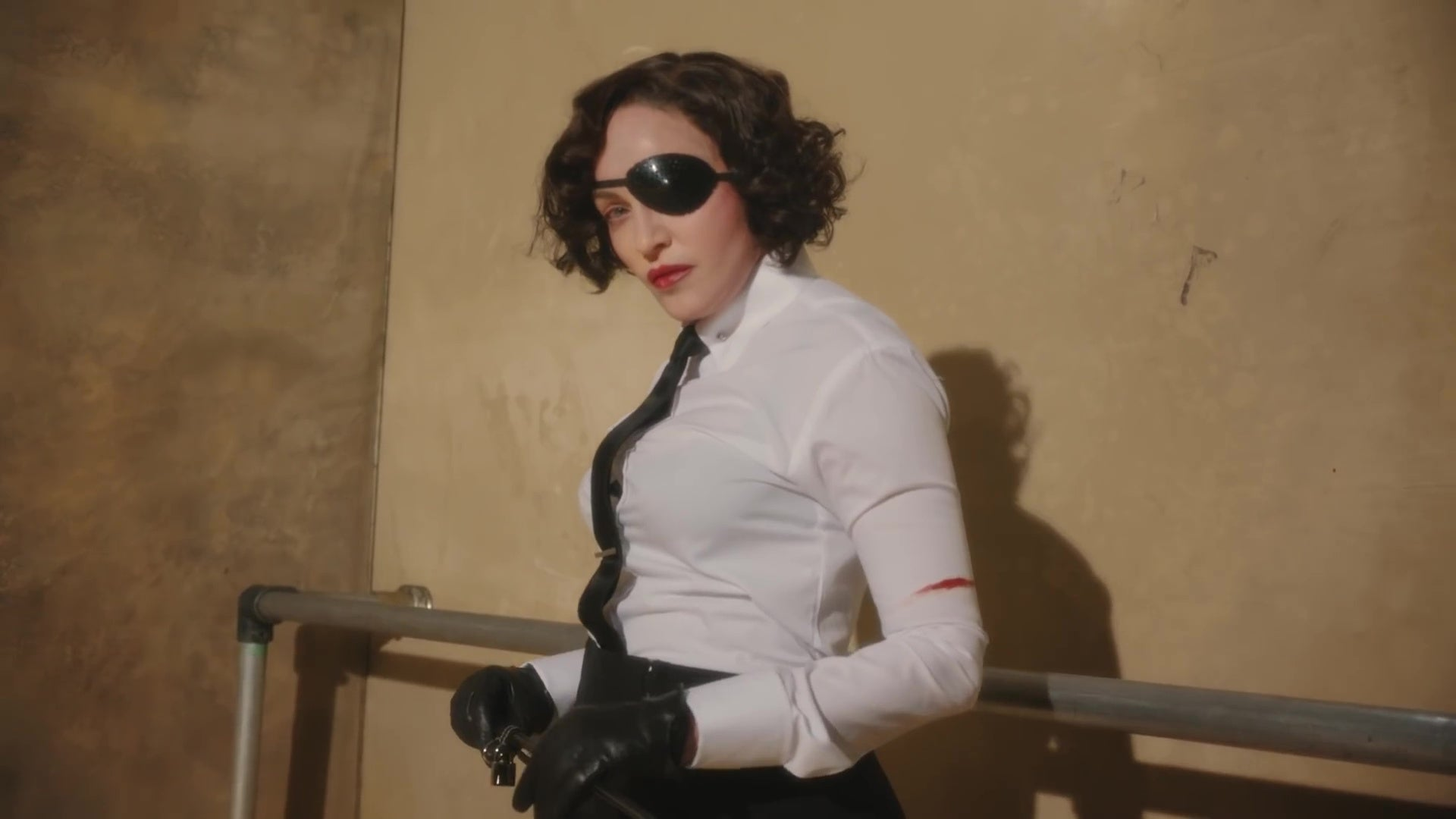 Madonna, in a white dress shirt, black tie, black eyepatch, and black leather gloves.