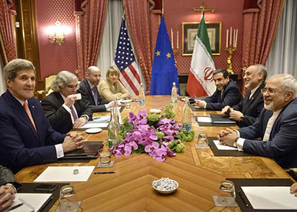 U.S. Secretary of State John Kerry (left) and Iranian Foreign Minister Mohammad Javad Zarif (right) wait with others for a meeting at the Beau-Rivage Palace Hotel on March 28, 2015, in Lausanne, Switzerland