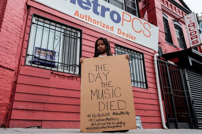 "Ryan-Camille Guyot holds a cardboard sign saying, ""The day the music died."""