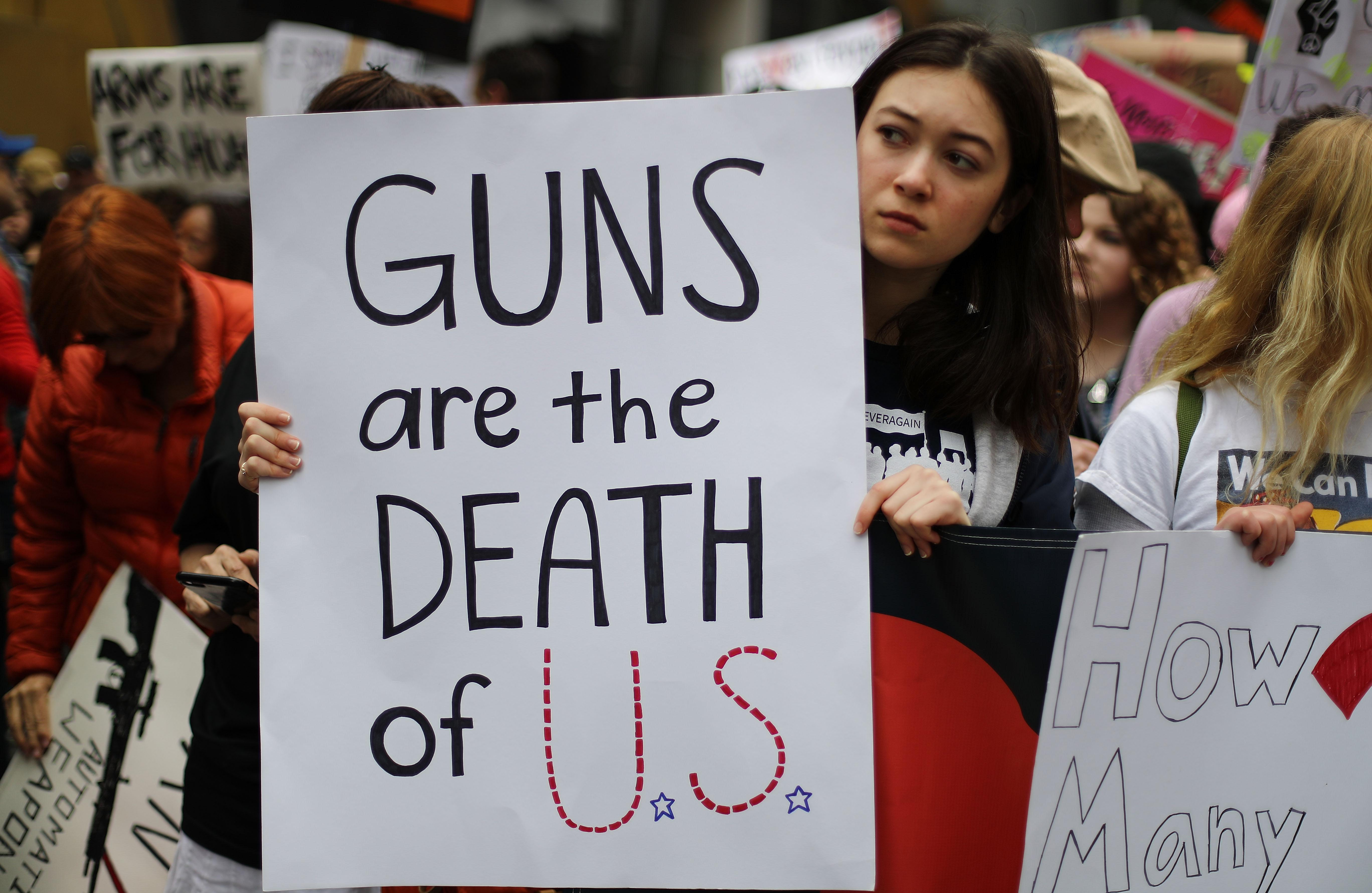 "A sign reads, ""Guns are the death of U.S."""