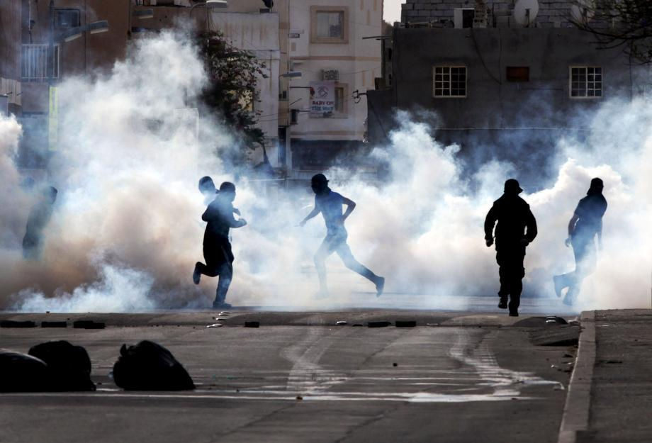 "Bahraini anti-government protesters react to tear gas fired by riot police in Sanabis, Bahrain, on March 14, 2013. Protests and clashes erupted in opposition areas nationwide Thursday with government opponents observing a ""Dignity Strike,"" blocking roads, closing shops, protesting, and staying home from work and school, called by the more radical February 14 youth group."