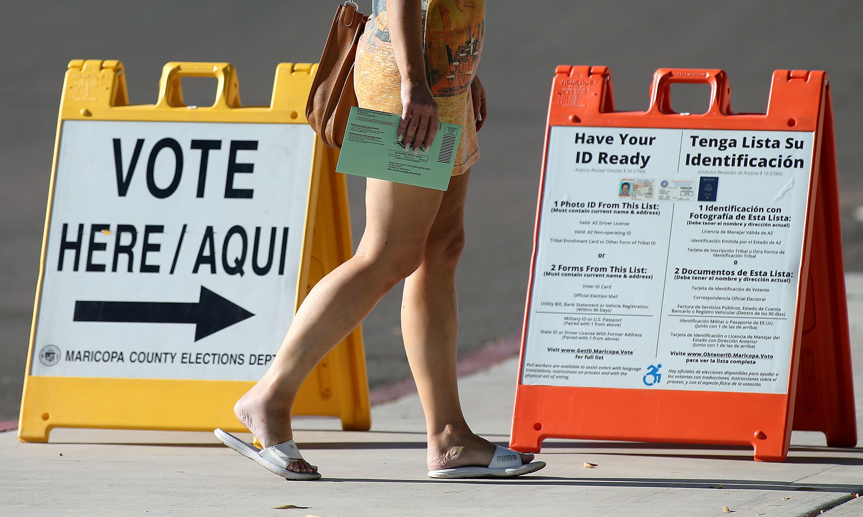 """An Arizona voter carries her ballot to a polling place, walking by a """"VOTE HERE"""" sign and a sign that tells voters to """"Have Your ID Ready."""""""