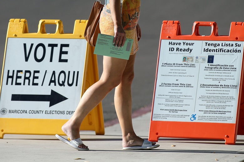 "An Arizona voter carries her ballot to a polling place, walking by a ""VOTE HERE"" sign and a sign that tells voters to ""Have Your ID Ready."""