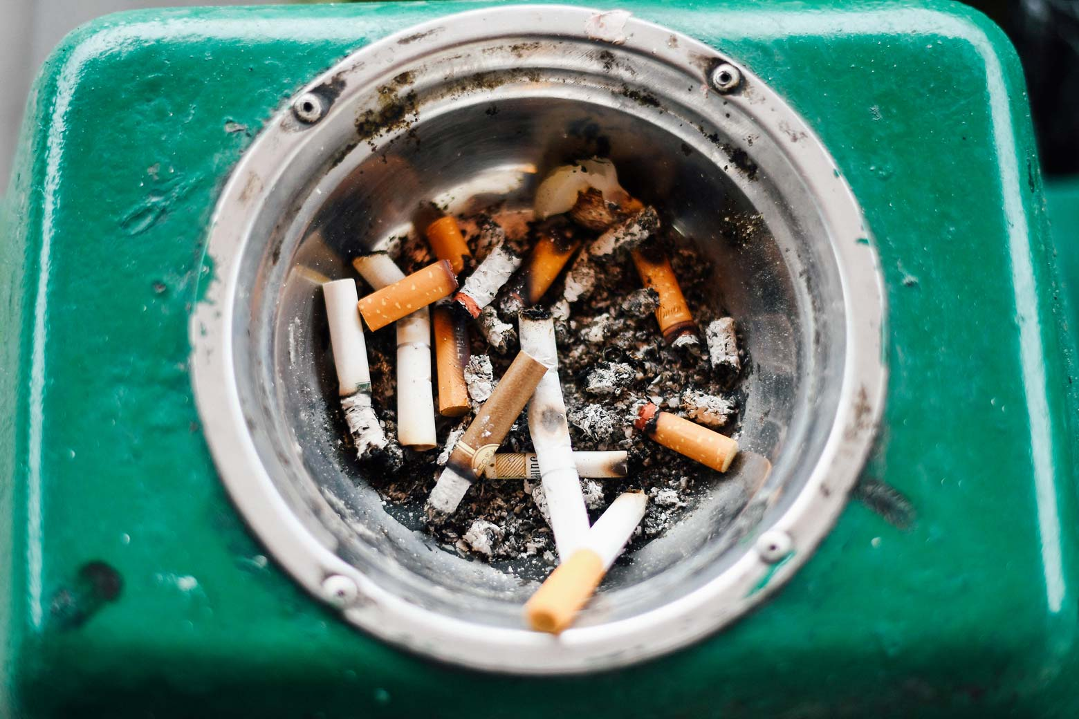 Used cigarette butts in a dirty ashtray.