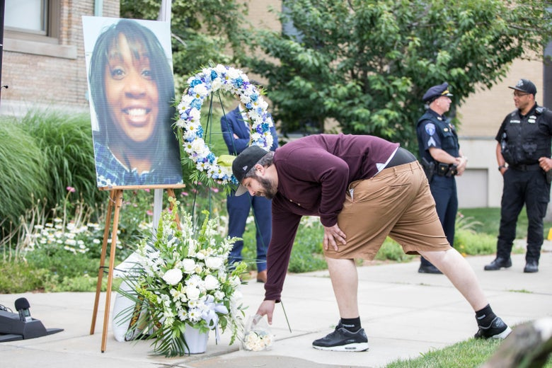 A man lays flowers in front of a photo of Ramona Cooper during a vigil held for two shooting victims on July 1, 2021 in Winthrop, Massachusetts.