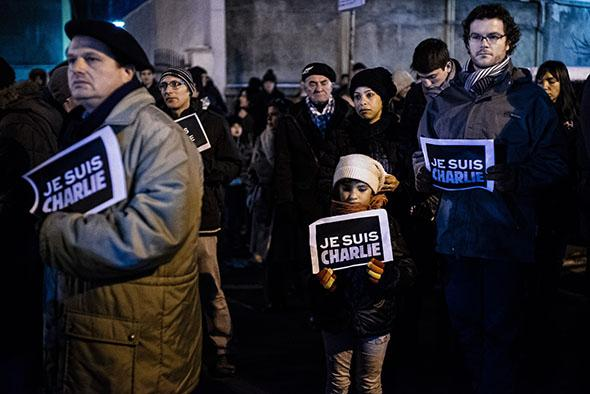 """People hold signs reading """"Je suis Charlie""""."""