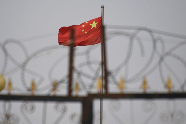 A Chinese flag seen behind razor wire.