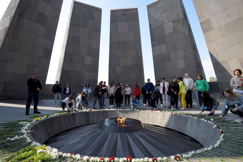 Armenians gathered around a commemorative flame, with tall stone slabs in the background.