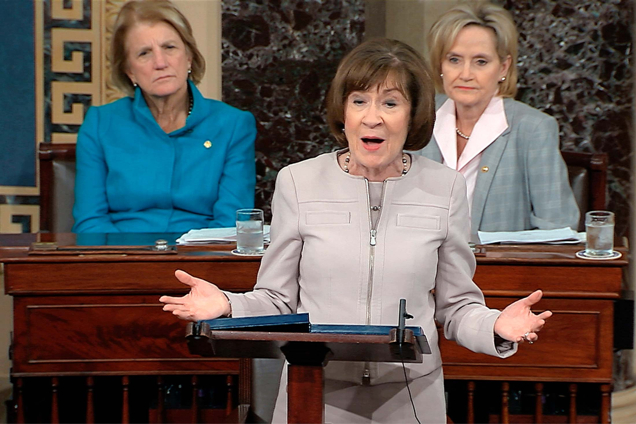 Susan Collins at a podium on the Senate floor with female senators behind her