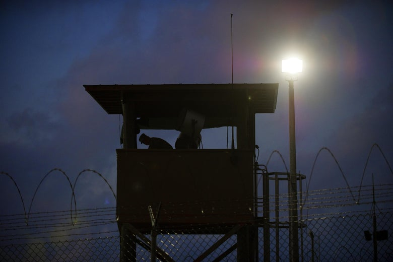 In this photo reviewed by US military officials, a member of the US military mans the guard post before sunrise at Camp Delta, part of the US Detention Center in Guantanamo Bay, Cuba,  March 30, 2010.    AFP Photo/Paul J. Richards (Photo credit should read PAUL J. RICHARDS/AFP/Getty Images)