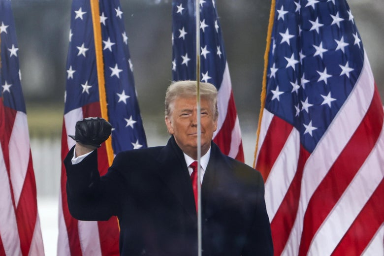 Trump smiles and makes a fist, standing onstage in front of American flags