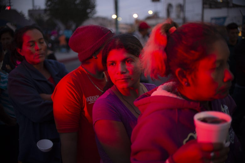 A woman looks out to the distance as a group of migrants, cast in a pink-hued light at night, wait for food.