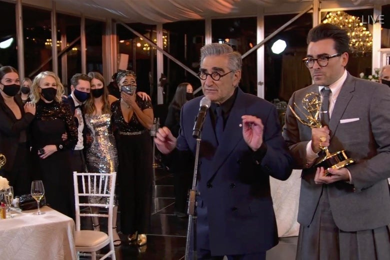 Eugene Levy and Dan Levy stand at the microphone as their Schitt's Creek comrades look on in masks.