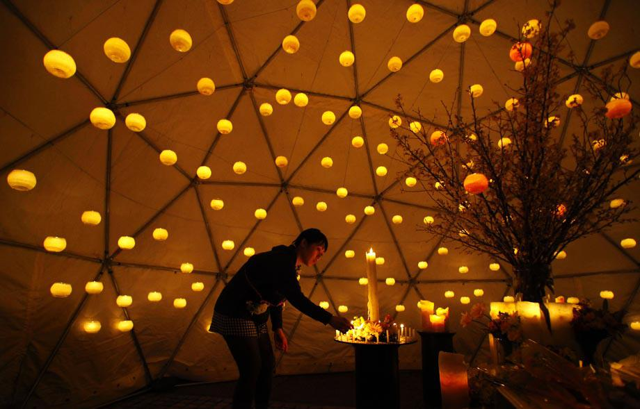 A woman lights candles to pay tribute to the victims of the March 11 earthquake and tsunami at a make-shift alter in a park in Tokyo.