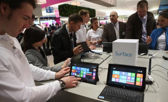 Visitors try out Windows 8 Surface tablet computers at the Microsoft stand at the 2013 CeBIT technology trade fair on March 5, 2013, in Hanover, Germany.