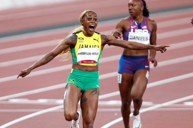 Thompson-Herah yells in celebration with her arms out to the side on the track, American Teahna Daniels in the background