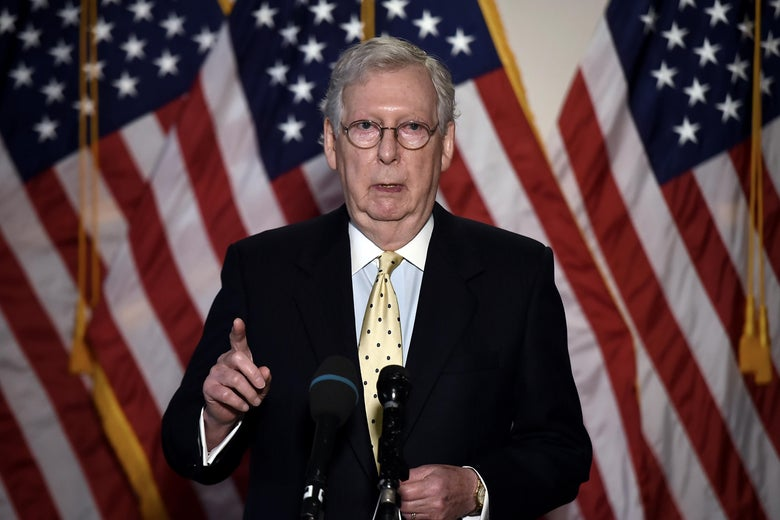 Mitch McConnell speaks into a microphone and points with American flags behind him.