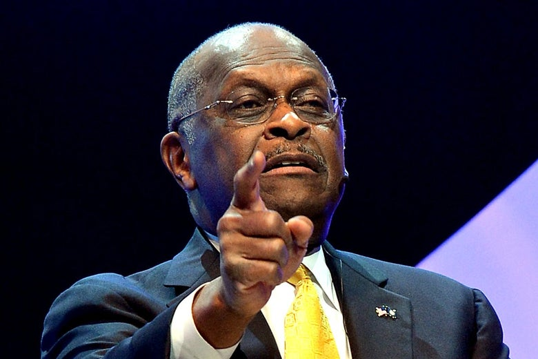 Herman Cain points toward the audience at a live talk.