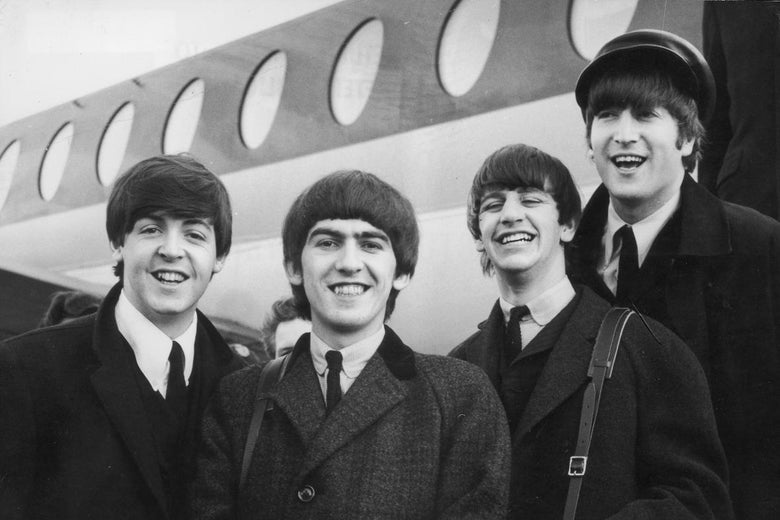 The Beatles, in black and white, standing in front of an airplane.