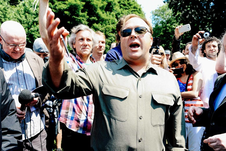 Alex Jones speaks to the media outside the Grove Hotel in Watford, England, where the Bilderberg Group summit meeting was held in 2013.