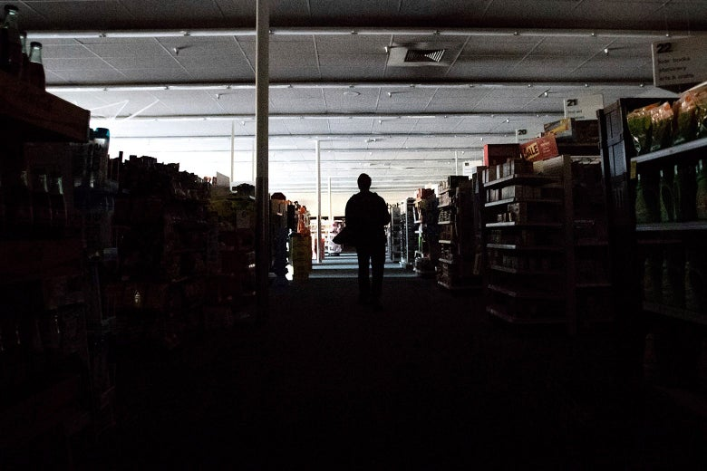 A man stands in the darkened aisles of a CVS.