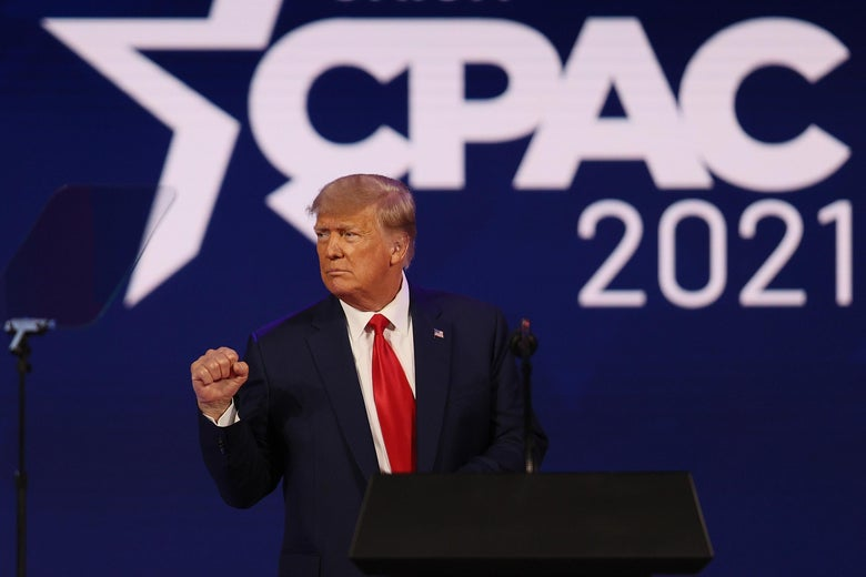 Trump pumping his fist onstage with the CPAC 2021 logo behind him