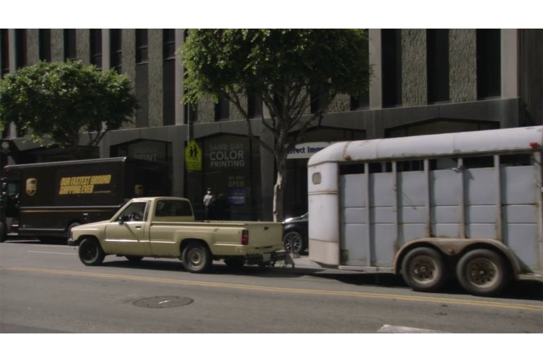 A pickup truck pulling a horse trailer down a Los Angeles street.