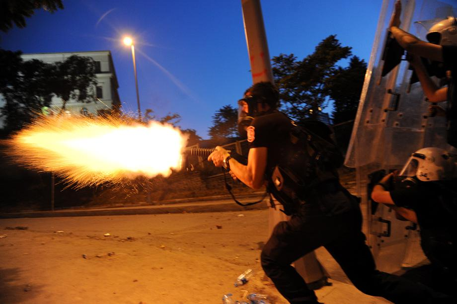 A Turkish riot police officer fires tear gas during clashes with protestors between Taksim and Besiktas in Istanbul on June 3, 2013.