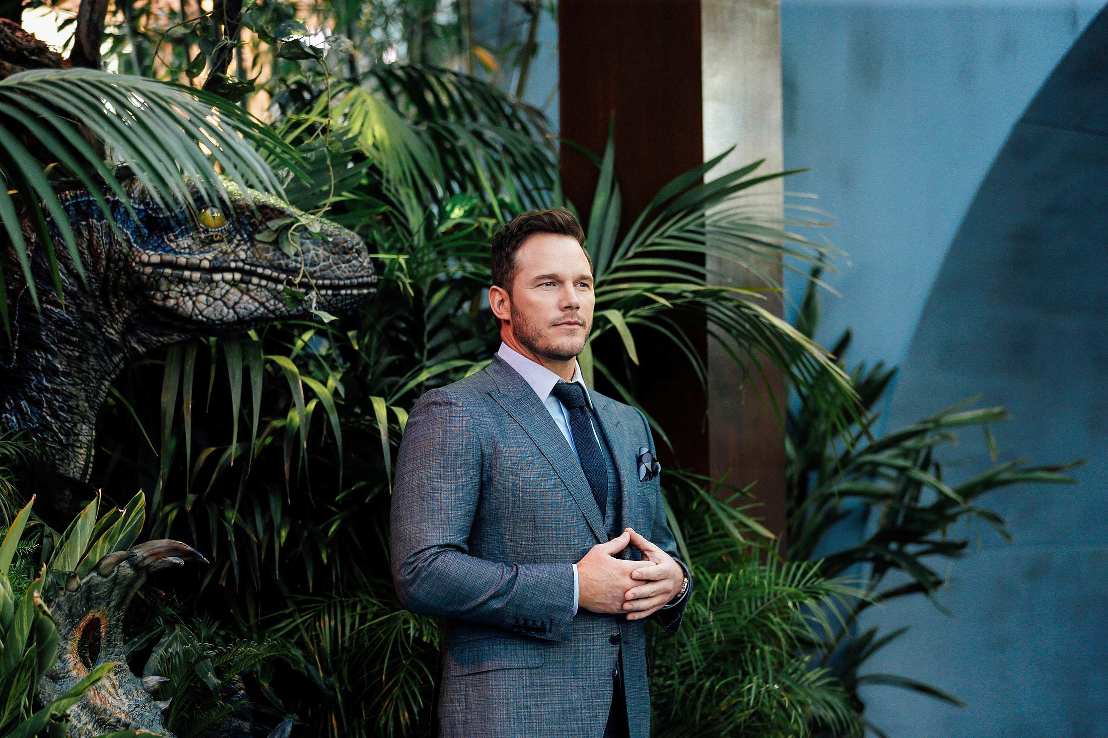 Chris Pratt stands looking solemn, wearing a suit with hands touching and thumbs tented, in front of a backdrop of tropical plants.
