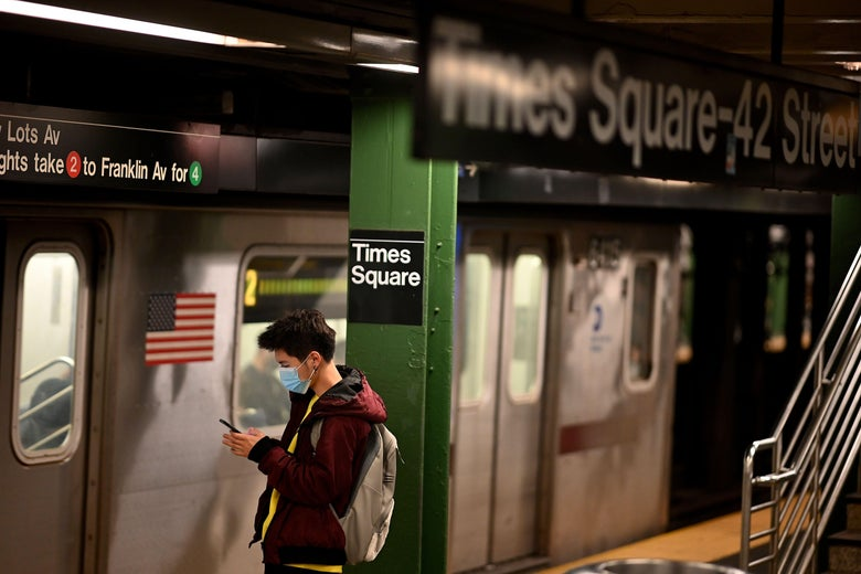 A man on a subway platform wearing a mask looks at his phone.