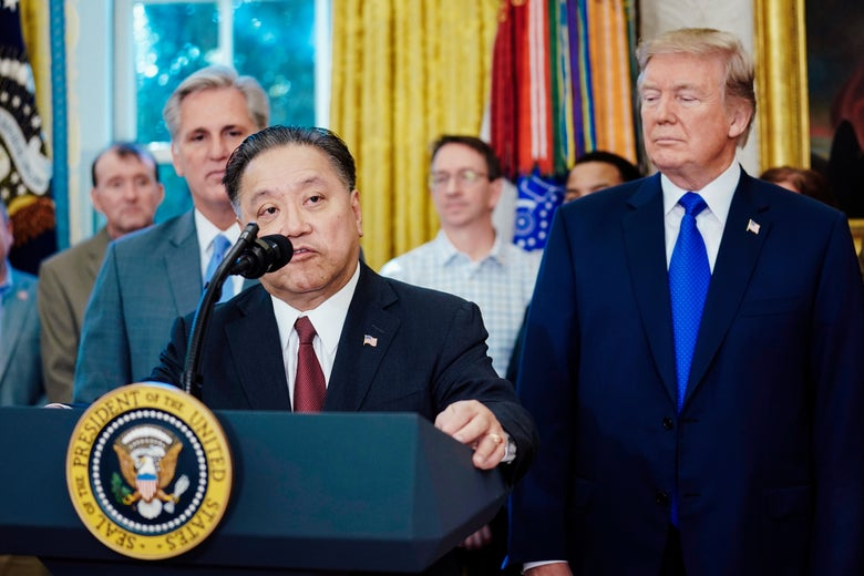 Hock Tan stands at a podium in the Oval Office as President Trump looks on.