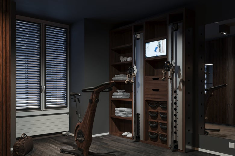 Exercise equipment and towels in a room with luxe wood paneling