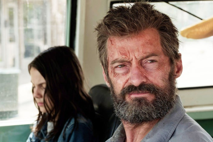 A battered-looking Hugh Jackman sits in a vehicle next to a young girl who is slightly out of focus.