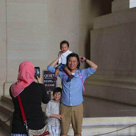 A tourist family pose for an iPhone photoshoot beneath the Lincoln Memorial.
