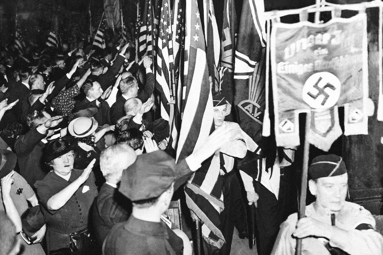 A black-and-white photo shows a crowd giving a Nazi salute to a swastika banner as it is carried past a row of U.S. flags.